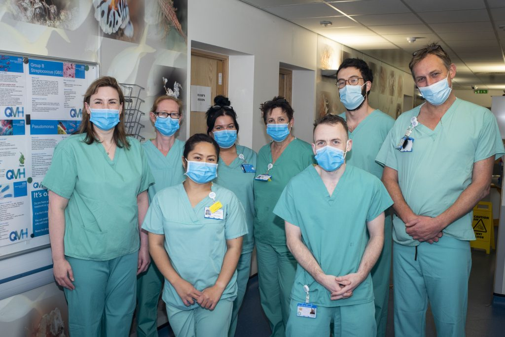 8 staff from the burns unit stand in a group wearing light green scrubs and face masks